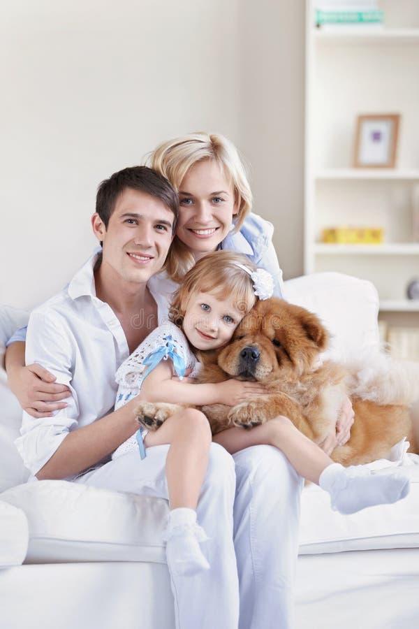 Lächelnde Familie mit einem Hund stockbilder