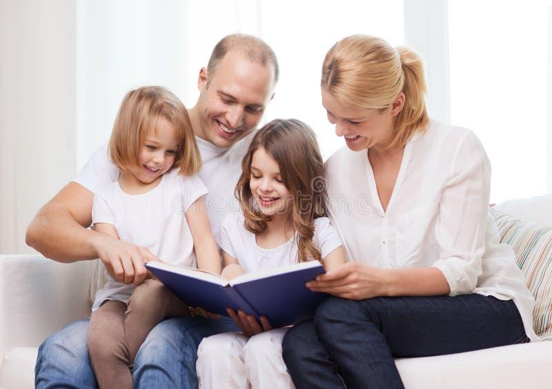 Lächelnde Familie und zwei kleine Mädchen mit Buch stockfoto