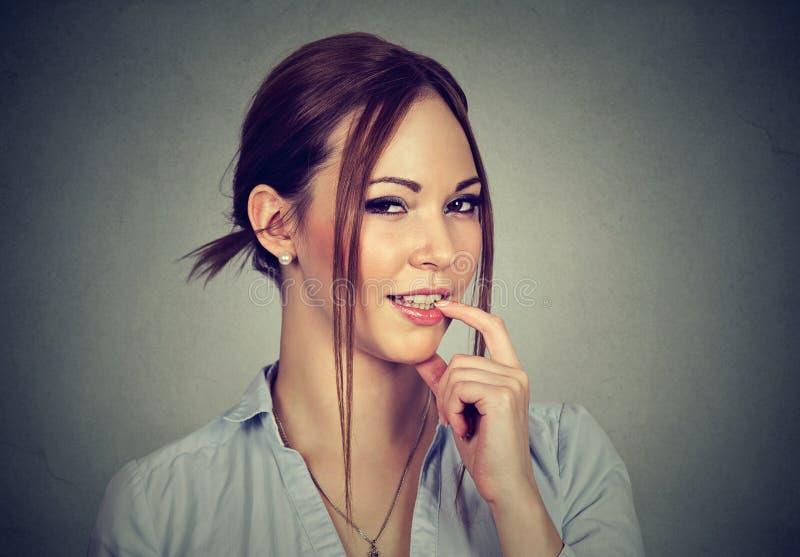 Lächelnde Flirtfrau mit dem Finger auf Lippe lizenzfreie stockbilder