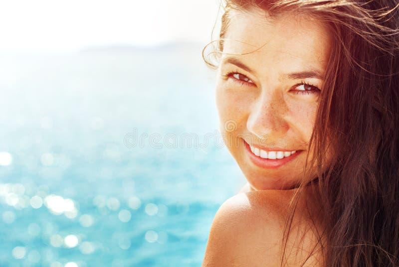 Lächelnde Frau auf dem Hintergrund vom blauen Meer in Sunlights Summ stockbild