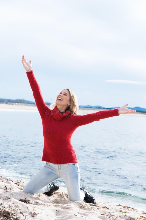 Lächelnde Frau auf dem Strand im Winter stockfotos
