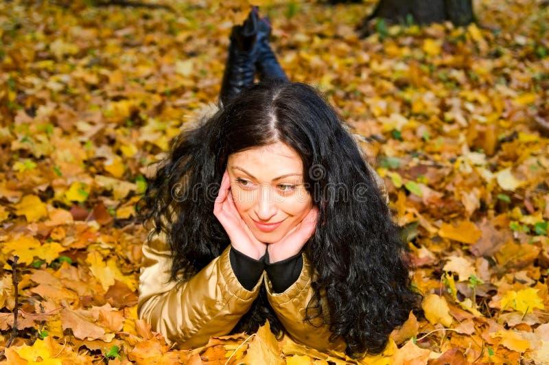 Lächelnde Frau auf Herbstblättern lizenzfreies stockbild