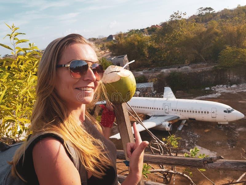 Lächelnde Frau bei der Aufstellung über verlassenem Flugzeug in Bali lizenzfreie stockbilder