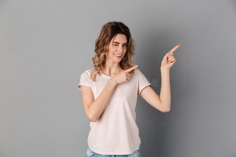 Lächelnde Frau beim T-Shirt Zeigen weg während Winks stockbild