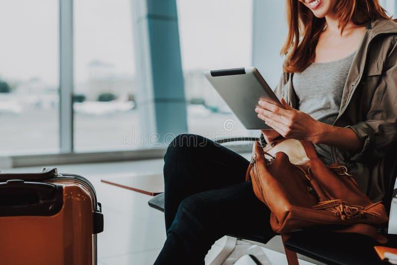 Lächelnde Frau benutzt Tablette am Flughafen lizenzfreies stockfoto