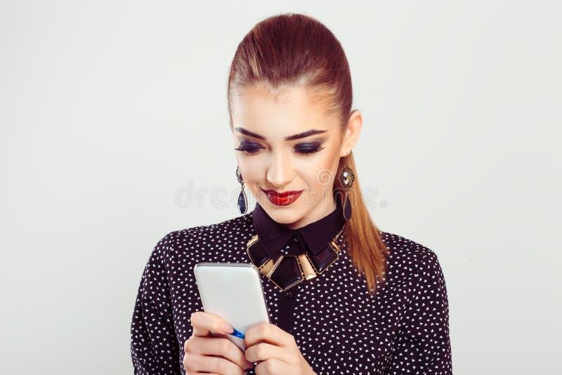 Lächelnde Frau betrachtet das Telefon aufgeregt erfreut durch den Mitteilungstext, den sie empfing stockbild