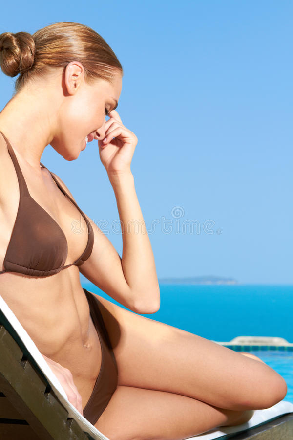 Lächelnde Frau in Brown-Bikini auf Strand-Stuhl lizenzfreie stockbilder