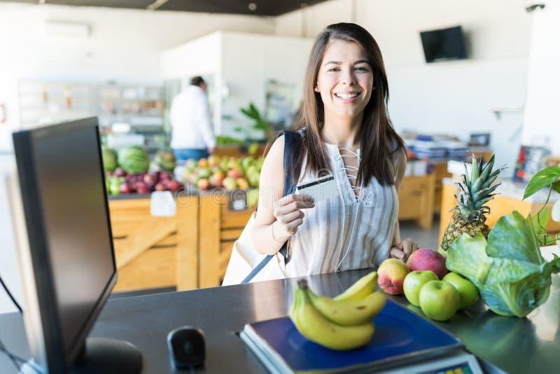 Lächelnde Frau an der Registrierkasse des Supermarktes lizenzfreies stockbild