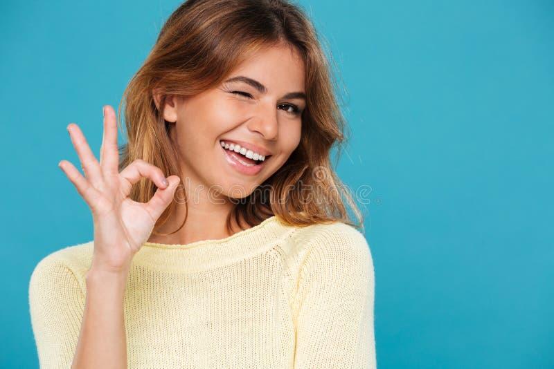 Lächelnde Frau in der Strickjacke, die okay Zeichen und Winks zeigt stockfotos