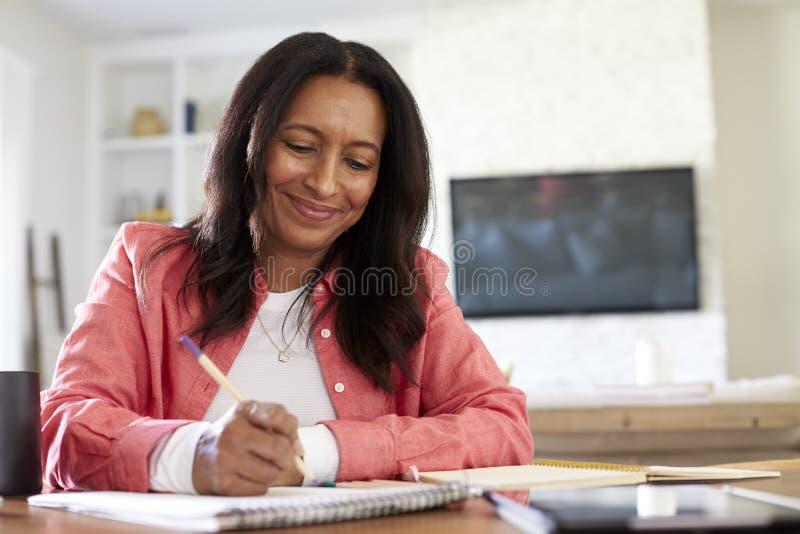 Lächelnde Frau des Afroamerikaners im Ruhestand, die an einem Tisch oben schreibt in ihr Esszimmer, Abschluss, niedriger Winkel s lizenzfreie stockfotografie