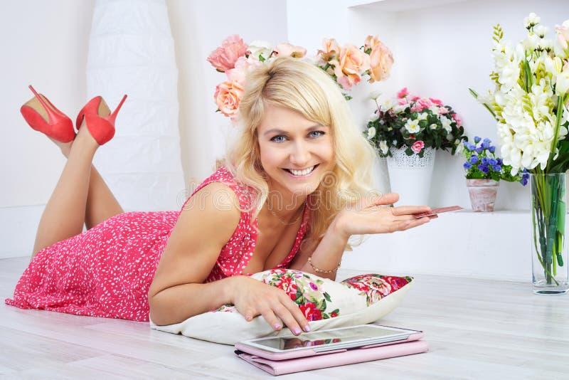 Lächelnde Frau, die auf Boden mit digitaler Tablette liegt lizenzfreie stockbilder