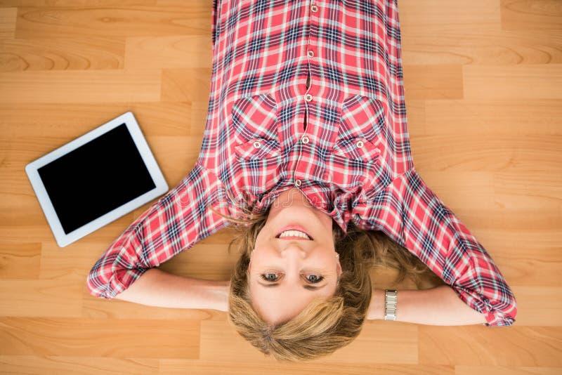 Lächelnde Frau, die auf Boden nahe bei Tablette liegt lizenzfreie stockfotos