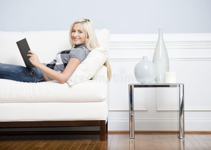 Lächelnde Frau, die auf Couch mit einem Buch stützt lizenzfreie stockfotos