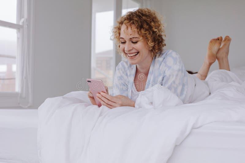 Lächelnde Frau, die auf dem Bett betrachtet ihren Handy liegt stockfotografie
