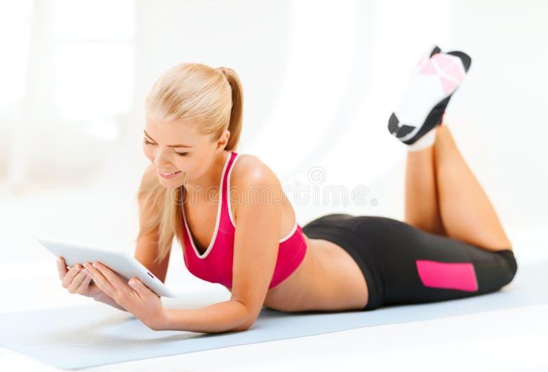 Lächelnde Frau, die auf dem Boden mit Tabletten-PC liegt stockbilder