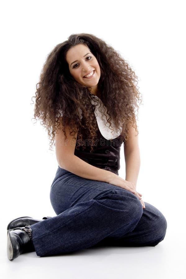Lächelnde Frau, die auf dem Fußboden sitzt stockfotos
