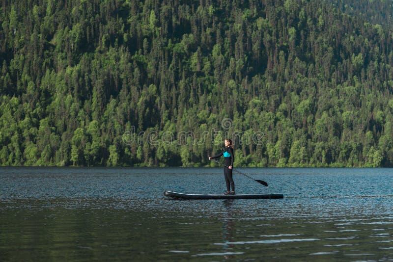 Lächelnde Frau, die auf dem Gebirgssee paddleboarding ist stockfoto