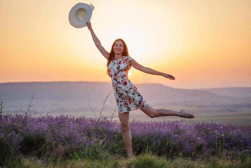Lächelnde Frau, die auf einem Bein auf Lavendelsonnenuntergang aufwirft lizenzfreies stockbild