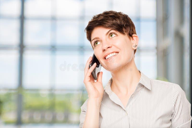Lächelnde Frau, die auf einem Handy spricht lizenzfreies stockbild