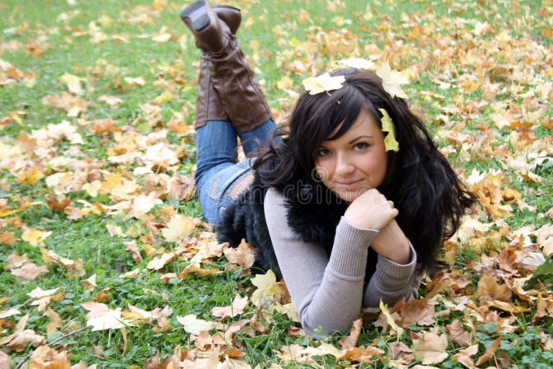 Lächelnde Frau, die auf einem Teppich der Blätter liegt stockbild