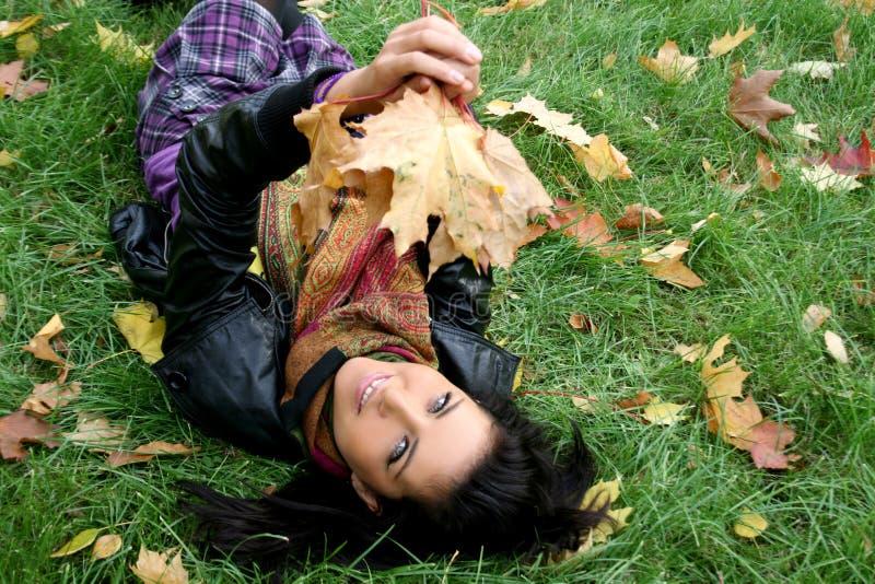 Lächelnde Frau, die auf einem Teppich der Blätter liegt stockfoto