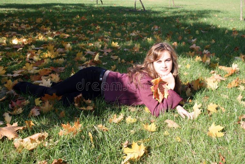 Lächelnde Frau, die auf einem Teppich der Blätter liegt lizenzfreie stockfotografie