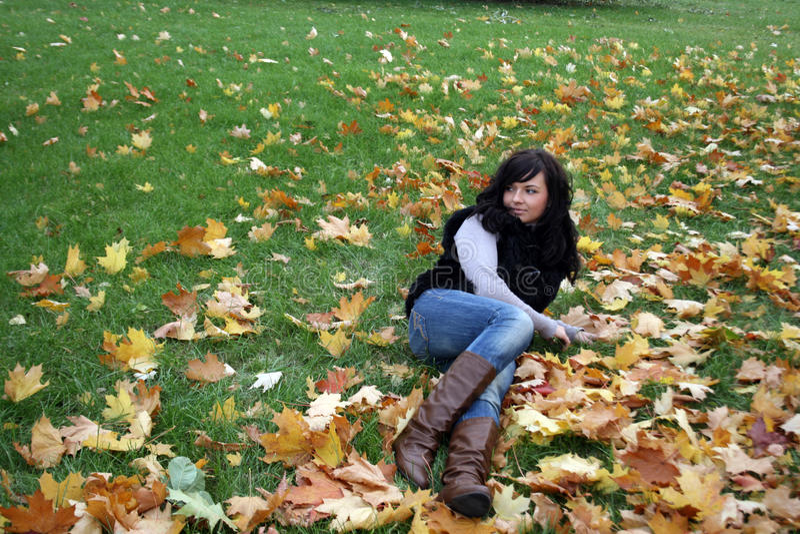 Lächelnde Frau, die auf einem Teppich der Blätter liegt lizenzfreie stockbilder