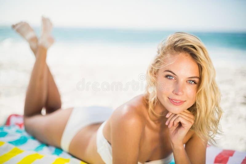 Lächelnde Frau, die auf einem Tuch am Strand liegt lizenzfreie stockfotografie