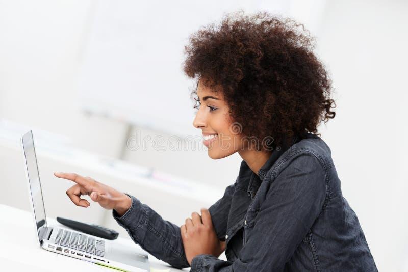 Lächelnde Frau, die auf ihren Laptopschirm zeigt stockfotos