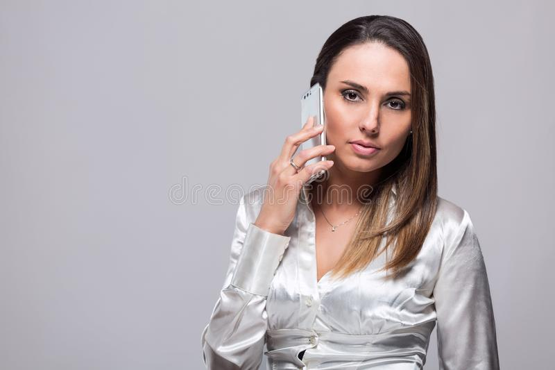 Lächelnde Frau, die auf Smartphone spricht lizenzfreie stockbilder