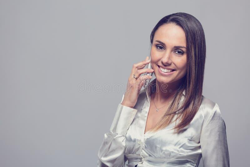 Lächelnde Frau, die auf Smartphone spricht stockfotos