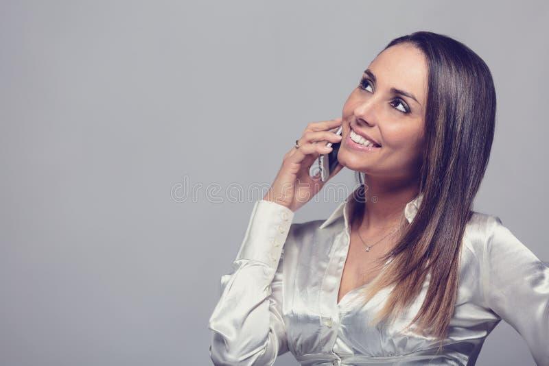 Lächelnde Frau, die auf Smartphone spricht stockfotografie