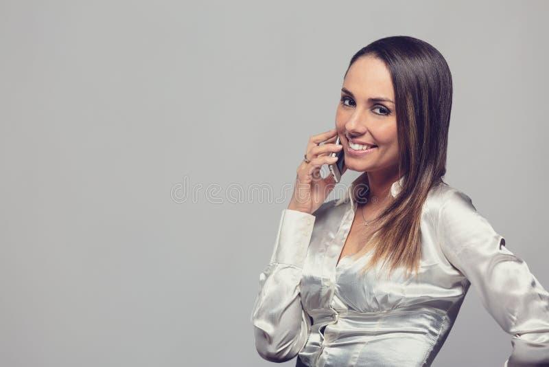 Lächelnde Frau, die auf Smartphone spricht lizenzfreie stockfotos