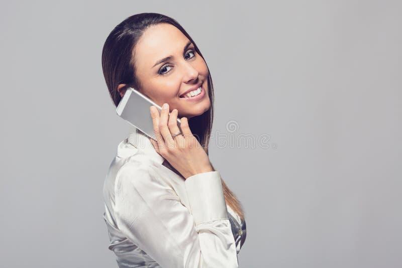 Lächelnde Frau, die auf Smartphone spricht stockfoto