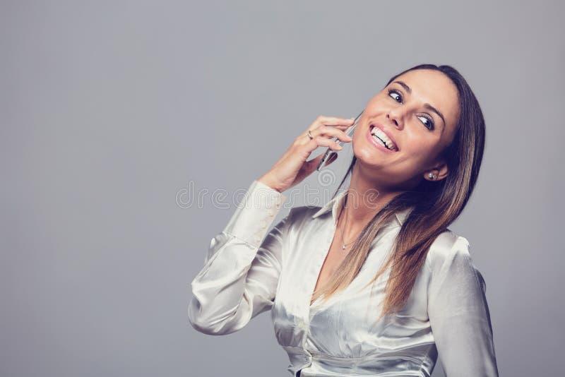 Lächelnde Frau, die auf Smartphone spricht stockbild