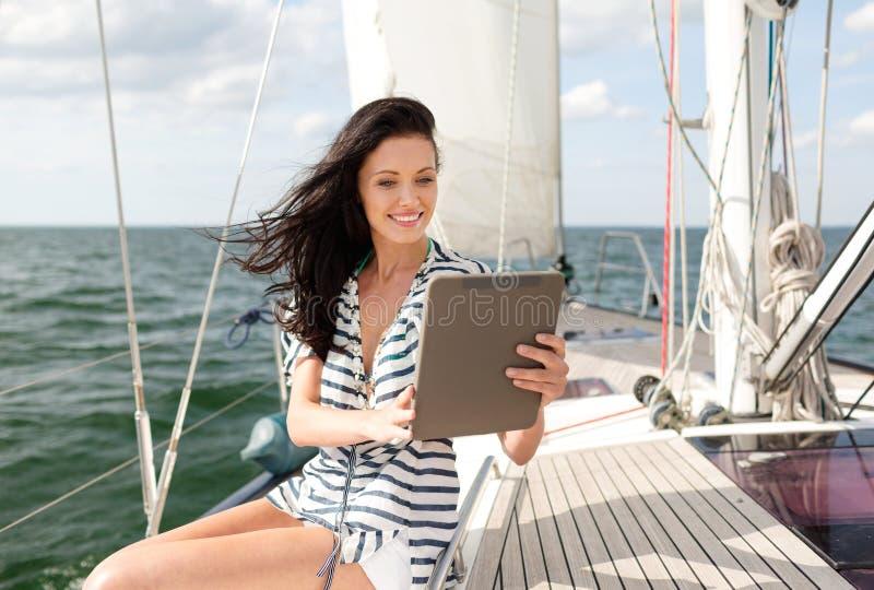 Lächelnde Frau, die auf Yacht mit Tabletten-PC sitzt lizenzfreies stockbild