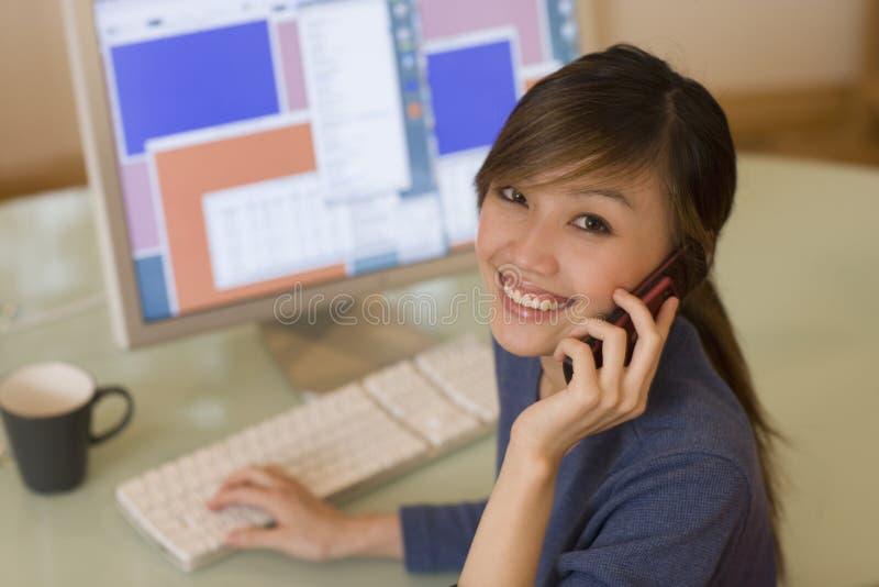 Lächelnde Frau, die Computer verwendet stockbild