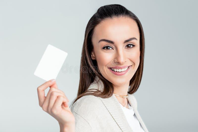 Lächelnde Frau, die in der Hand Kreditkarte hält und zur Kamera schaut lizenzfreie stockfotos