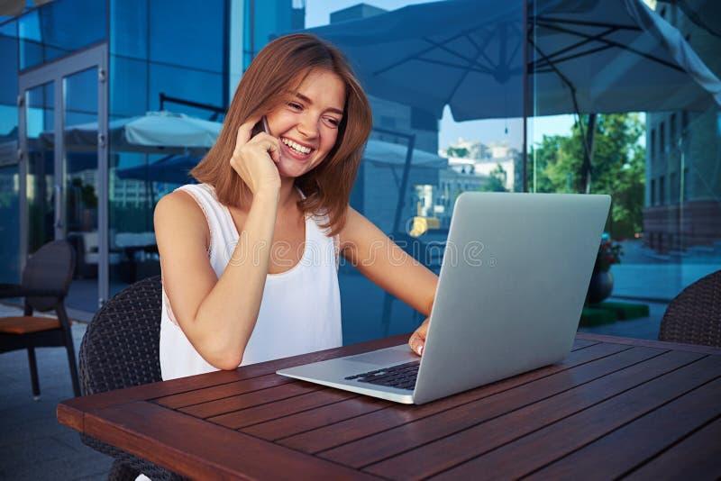 Lächelnde Frau, die drahtloses Internet auf Laptop im Freilicht CAF verwendet stockbilder