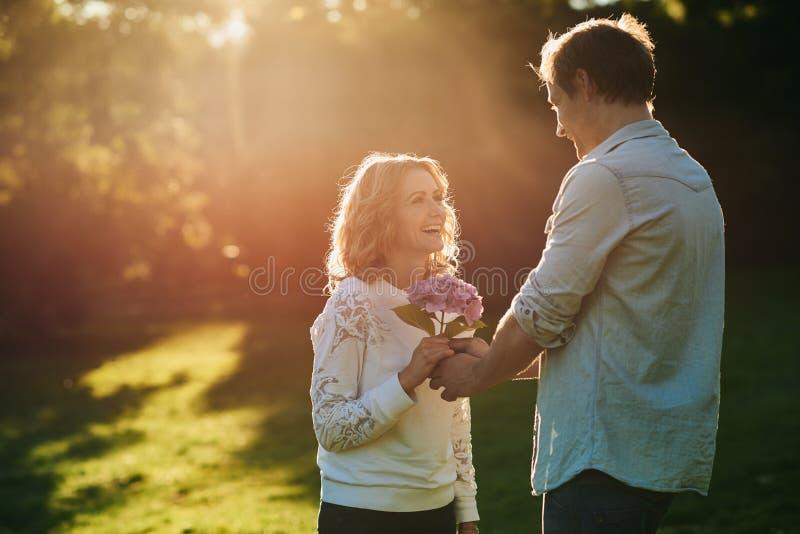 Lächelnde Frau, die draußen Blumen von ihrem Ehemann empfängt stockfotografie