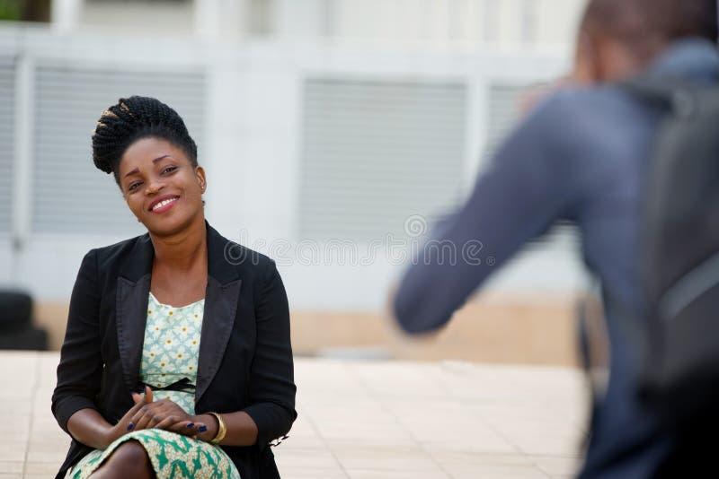 Lächelnde Frau, die draußen für den Fotografen aufwirft stockfotos