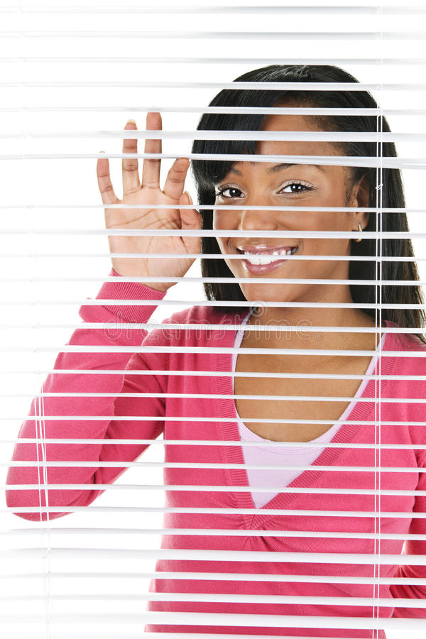 Lächelnde Frau, die durch Vorhänge schaut lizenzfreie stockbilder