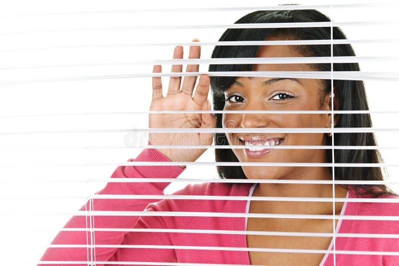 Lächelnde Frau, die durch Vorhänge schaut stockfoto