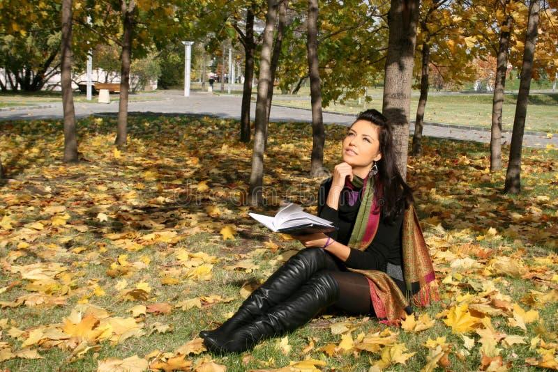Lächelnde Frau, die ein Buch liest stockfotos