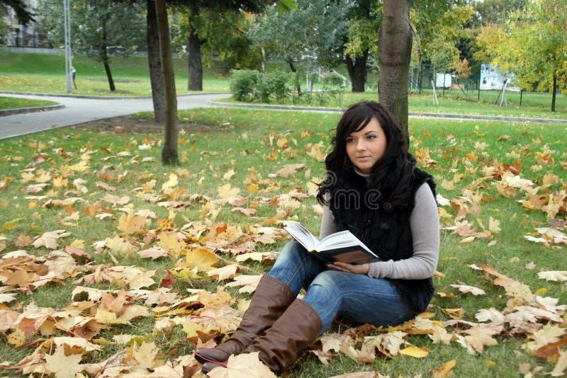 Lächelnde Frau, die ein Buch liest lizenzfreies stockfoto