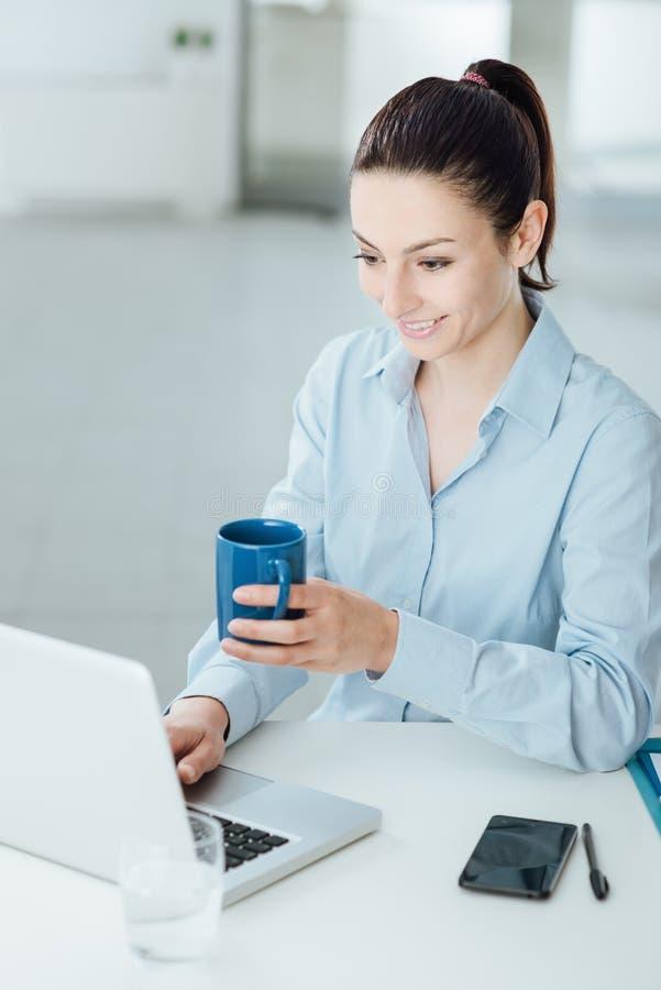 Lächelnde Frau, die eine Kaffeepause hat stockbilder
