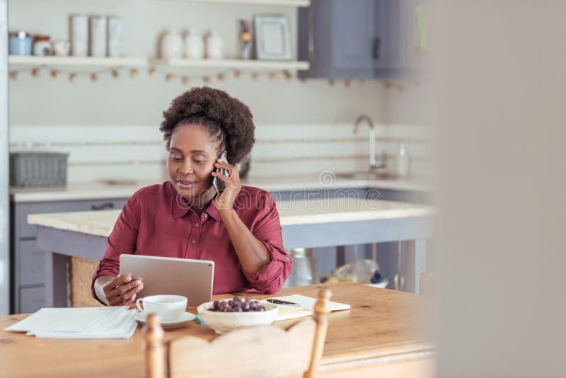 Lächelnde Frau, die eine Tablette verwendet und am Telefon spricht stockfotografie