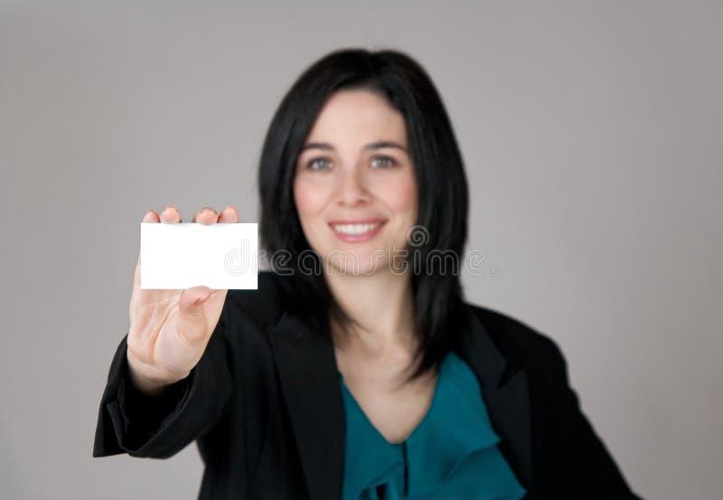 Lächelnde Frau, die eine Visitenkarte zeigt lizenzfreie stockfotografie