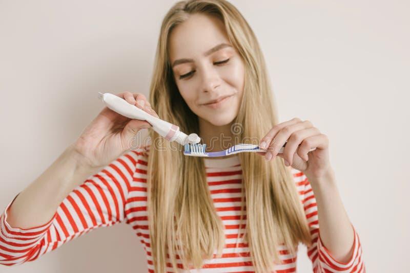 Lächelnde Frau, die eine Zahnbürste hält und die Zahnpasta lokalisiert auf einen weißen Hintergrund setzt lizenzfreies stockfoto