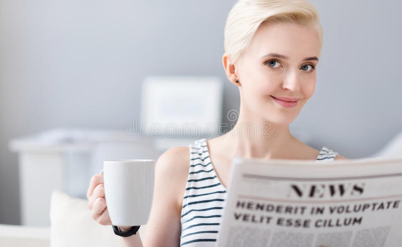 Lächelnde Frau, die eine Zeitung liest stockbild